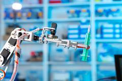 Robot holding a medical syringe Stock Photos