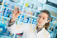 woman laboratory assistant draws a graph on a glass - stock photo