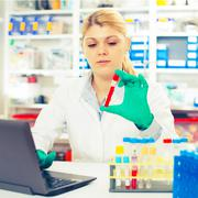 a woman laboratory assistant uses a computer research blood sample - stock photo