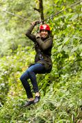 Stock Photo of Adult Slim Afro Woman On Zip Line In Ecuadorian Rainforest Nearby Banos De Agua