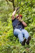 Oversized Adult Man On Zip Line Or Canopy Trip Nearby Of Banos De Agua Santa Stock Photos