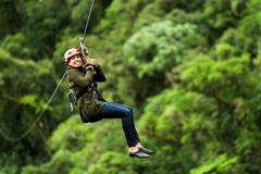 Adult Slim Afro Woman On Zip Line In Ecuadorian Rainforest Nearby Banos De Agua - stock photo