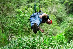 Oversized Adult Man On Zip Line Or Canopy Trip Nearby Of Banos De Agua Santa - stock photo