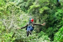 Stock Photo of Adult Slim Afro Woman Close Up Portrait On Zip Line In Ecuadorian Rainforest