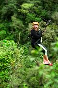 Oversized Adult Woman On Zip Line Trip Selective Focus Against Blurred Rain Stock Photos