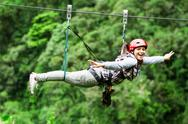 Stock Photo of Adult Tourist Wearing Casual Clothing On Zip Line Trip Selective Focus Against