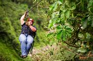 Stock Photo of Oversized Adult Man On Zip Line Or Canopy Trip Nearby Of Banos De Agua Santa