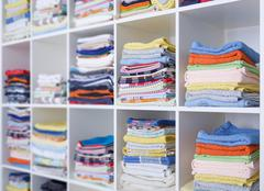 towels, bed sheets and clothes on the shelf - stock photo