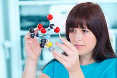 Girl student holding a model of chemical molecules Kuvituskuvat