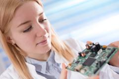 Girl student studying electronic device with a microprocessor Kuvituskuvat