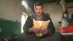 Afghan prepares bread in a food market stand in Kabul Afghanistan Stock Footage
