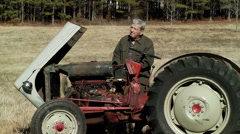 Stock Video Footage of old farmer with tractor waves to neighbor