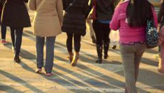 Pedestrians crossing street afternoon sunset long shadows Stock Footage