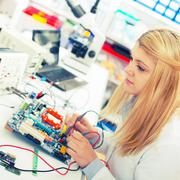 Girl with a tester and a printed circuit board Kuvituskuvat