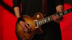 Guitar player on a red background Stock Footage
