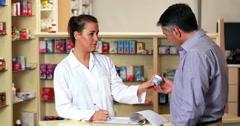 Pharmacist advising customer on medicine - stock footage