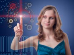 young woman presses the button on the high-tech screen - stock photo