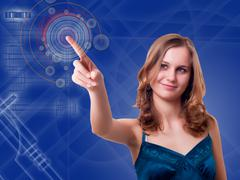 Young woman presses the button on the high-tech screen Stock Photos