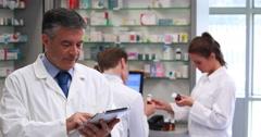Senior pharmacist using tablet pc Stock Footage