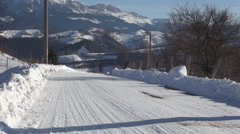 Road snow cover in a sunny day in a mountain village. - stock footage