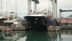 Crane leans maxi yacht on the water during launch Stock Footage