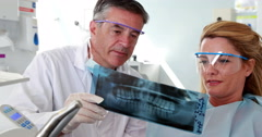 Dentist and patient in protective glasses looking x-ray together Stock Footage