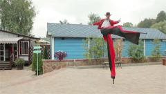 Stilt walker in red costium dancing and running Stock Footage