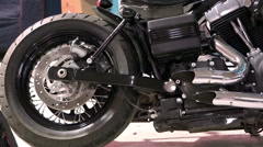Wheel spokes engine exhaust system sports a black motorcycle on display. Stock Footage
