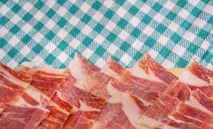 Top view of Serrano ham slices over plate and tablecloth - stock photo