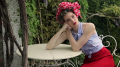 Beautiful Fashion Model Wearing Hair Curlers And Headscarf Sits In Garden - stock footage