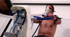 Fit man doing a stress test on exercise bike Stock Footage