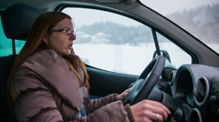 Woman driving car in snow Stock Footage