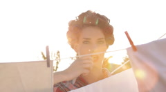 Fashion Beauty Wearing Hair Curlers Is Hanging Laundry In Sun Flared Garden Stock Footage