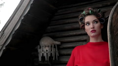 Fashionable Young Woman With Hair Curlers In Hair Stands Outside The Cottage Stock Footage