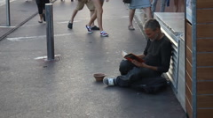 Homeless man reading a book on the street Stock Footage