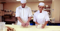 Culinary students kneading dough together Stock Footage