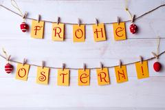 german frohe ostern which means happy easter hanging on line four easter eggs - stock photo