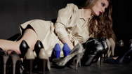 Stock Video Footage of Fashion Model Poses With Multiple high heel Shoes In Foreground