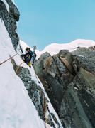 ice climbing: mountaineer on a mixed route of snow and rock during the winter - stock photo