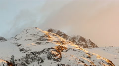 Alps sunset clouds moving over a snowy mountain range uhd 4k Stock Footage