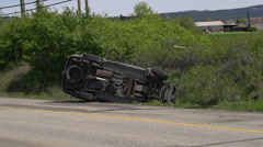 Auto accident, rolled SUV cu, along country road Stock Footage
