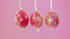 Eastern handmade traditional eggs hanging on rope with pink background Stock Footage