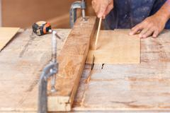 carpenter use saw cut wood for make new furniture - stock photo