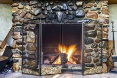 Stock Photo of stone fireplace in country house and fire blazing inside with natural light