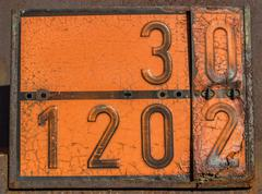 Old and rusty orange plate with hazard identification number Stock Photos