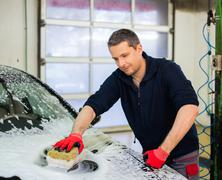 Man worker washing luxury car with sponge on a car wash Stock Photos