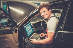Serviceman making car diagnostics with laptop in a workshop Stock Photos