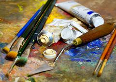 Artistic equipment: paint, brushes, spatula and art palette Stock Photos