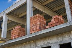stacked red hollow clay blocks for building block walls - stock photo