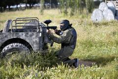 Protective sport player in uniform and mask Aiming gun, behind a jeep Stock Photos